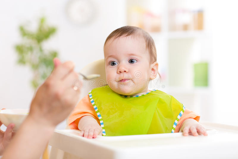 Mamy żywieniowy dziecko z łyżką zdjęcia royalty free