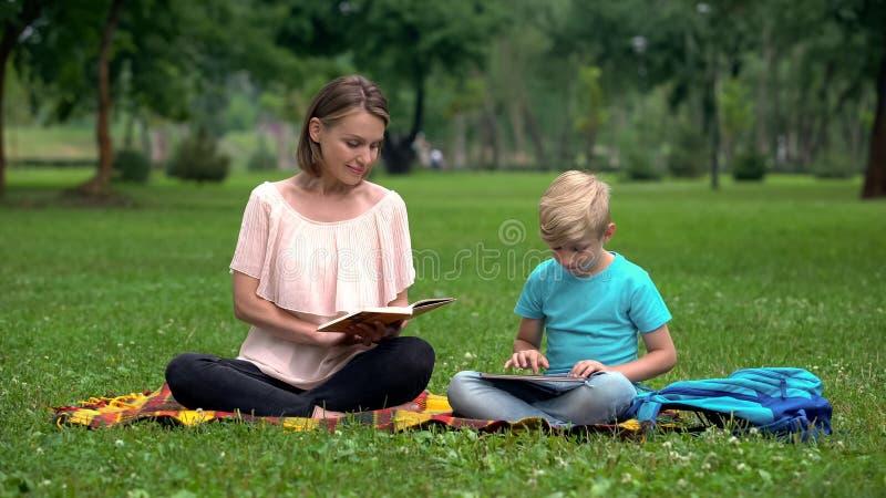 Mamy czytelnicza książka, syn używa pastylkę, alternatywna edukacja z IT technologiami obraz stock
