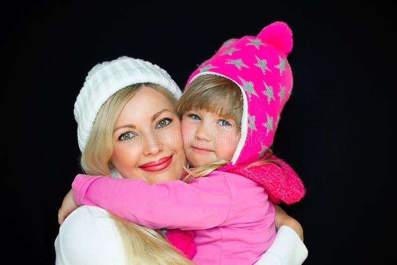 Mamy i córki uścisk w trykotowych kapeluszach na czarnym tle, Szczęśliwa rodzina, uśmiechy i radość, zdjęcia royalty free