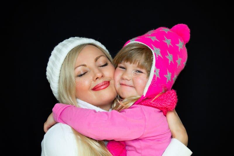 Mamy i córki uścisk w trykotowych kapeluszach na czarnym tle, Szczęśliwa rodzina, uśmiechy i radość, zdjęcie royalty free