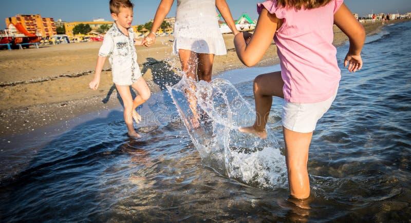 Mamy i dzieci sztuka z wodą przy morzem obraz stock
