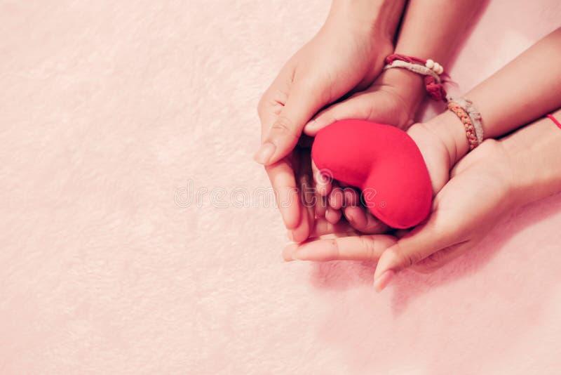 Mamy i dzieciaka ręki trzyma czerwonego serce mały dla dnia pojęcia valentine miłości zdjęcia stock