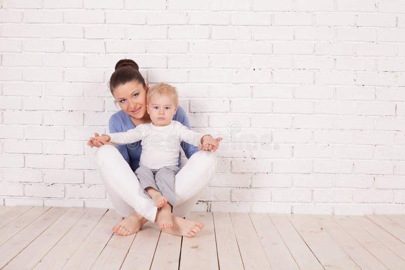 Mamy i potomstwo chłopiec obsiadanie na podłoga zdjęcia royalty free