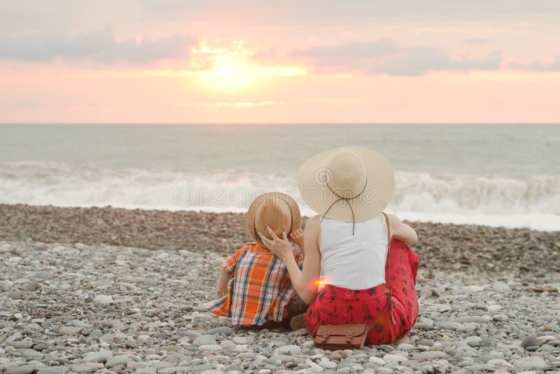 Mamy i syna obsiadanie na plaży i podziwia zmierzch Plecy rywalizuje obraz royalty free