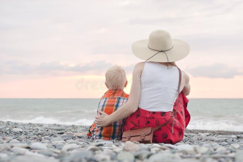 Mamy i syna obsiadanie na plaży i podziwia zmierzch Plecy rywalizuje zdjęcie stock