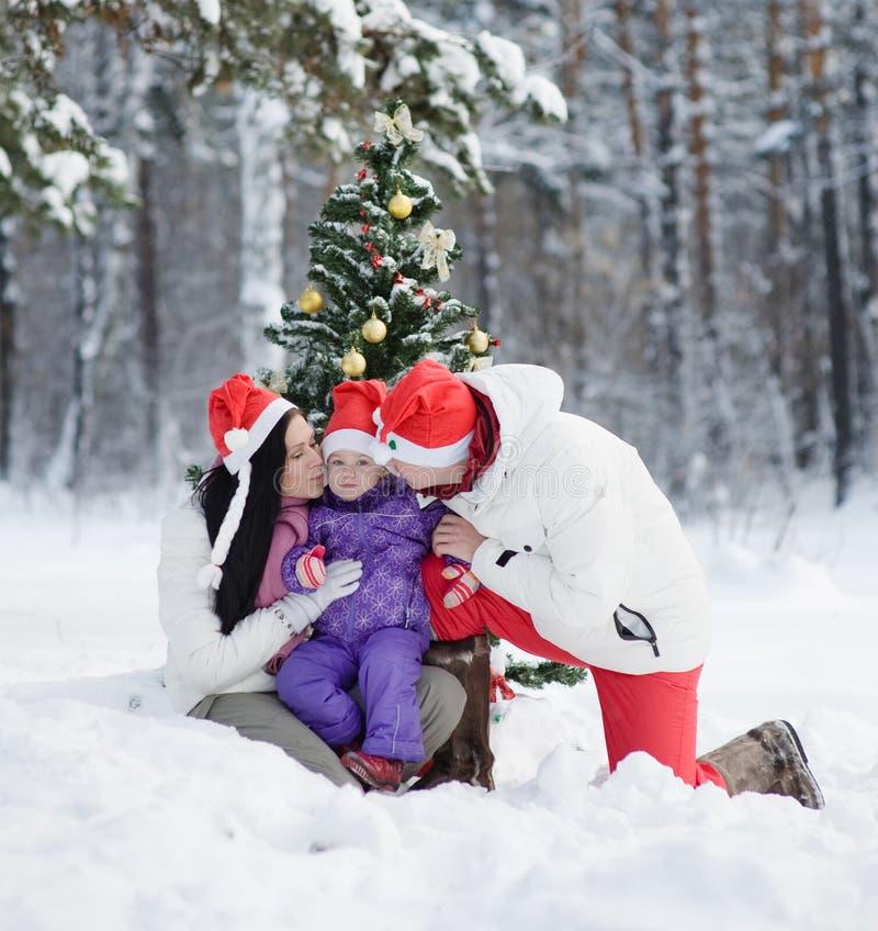 Mamy i tata całowania córka blisko choinki w zima lesie zdjęcie royalty free