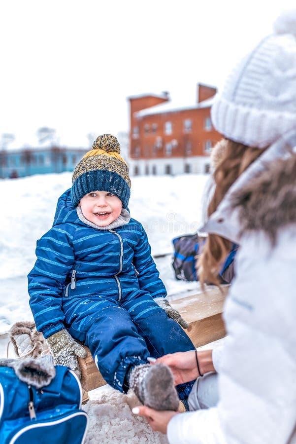 Mamy kobieta kuje skarpety na łyżwach chłopiec i kombinezony, troszkę 2-3 roku w zima kapeluszu Pojęcie opieka i poparcie przy zdjęcia royalty free