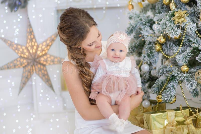 Mamy matka z słodką i piękną córką troszkę wydaje czas sztuki, gruchy, siedzi obok choinki zdjęcie royalty free