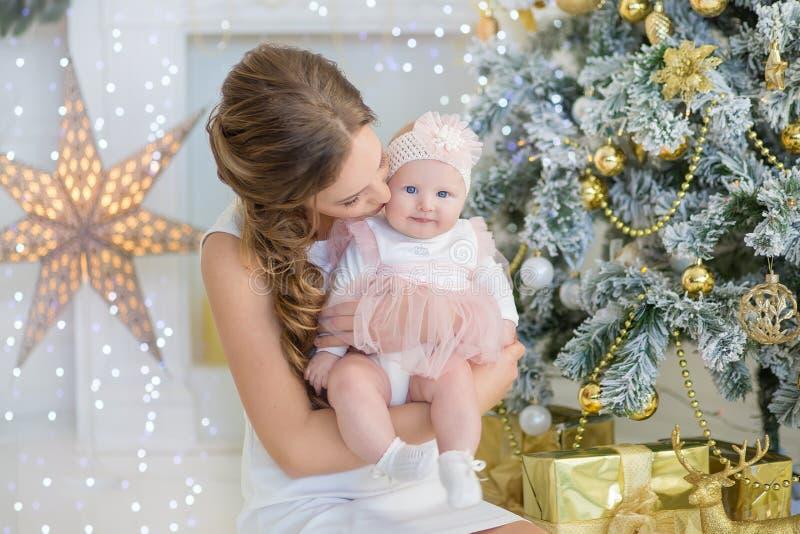 Mamy matka z słodką i piękną córką troszkę wydaje czas sztuki, gruchy, siedzi obok choinki zdjęcia royalty free