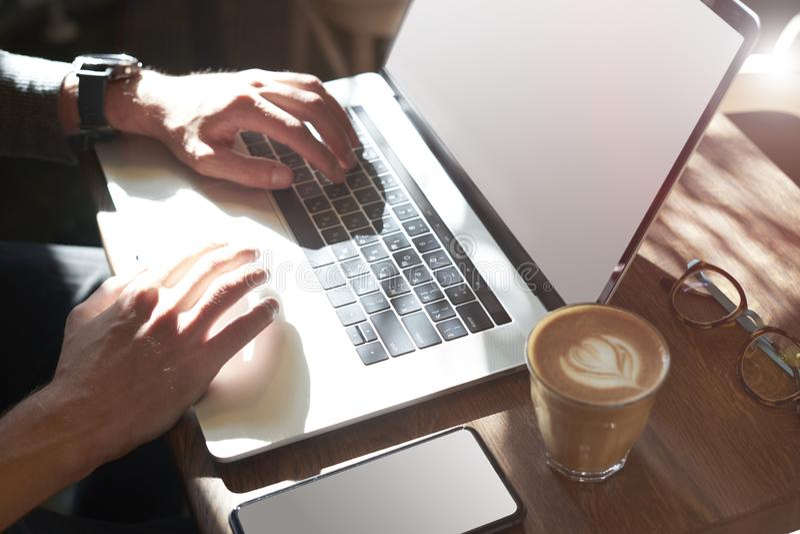 man's手特写镜头在膝上型计算机键盘的 使用计算机和智能手机的人坐在食用的咖啡馆咖啡 布局的空间 免版税库存照片