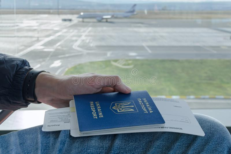 Man's hand is holding Ukrainian foreign passport with tickets to airplane in background parked plane. Tbilisi, Georgia, 2017-12-07: Man's hand is stock photo