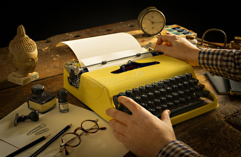 Man's hands typing on a vintage yellow typewriter on an wooden desk royalty free stock image