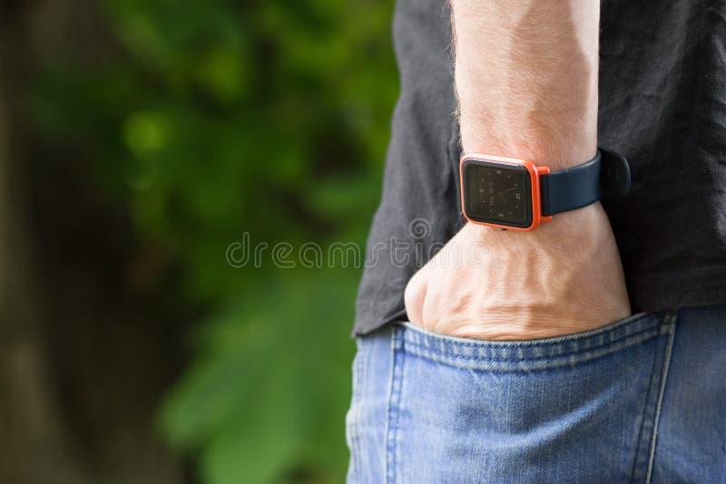 Man's ręka w cajgach wkładać do kieszeni z mądrze zegarkiem na jego nadgarstek zieleni i natury drzew bokeh tle obraz stock