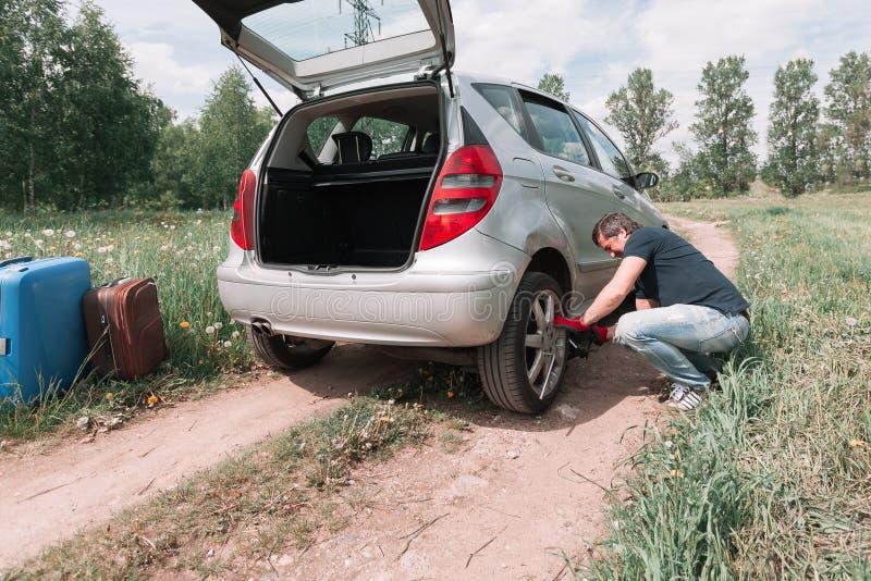 Manändringar ett plant gummihjul på hans bil arkivbilder