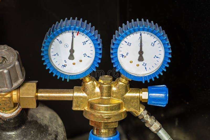 Manómetro o indicador de presión con el reductor del cilindro de la válvula y de gas fotografía de archivo