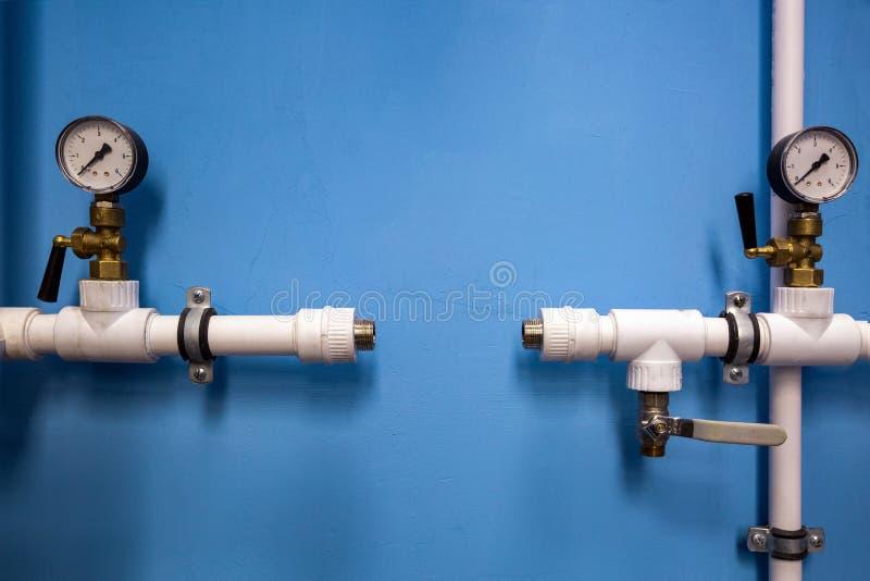 Manómetros del sistema que sondea de centro con los indicadores de la presión sobre los tubos de agua plásticos del sistema de fo fotos de archivo