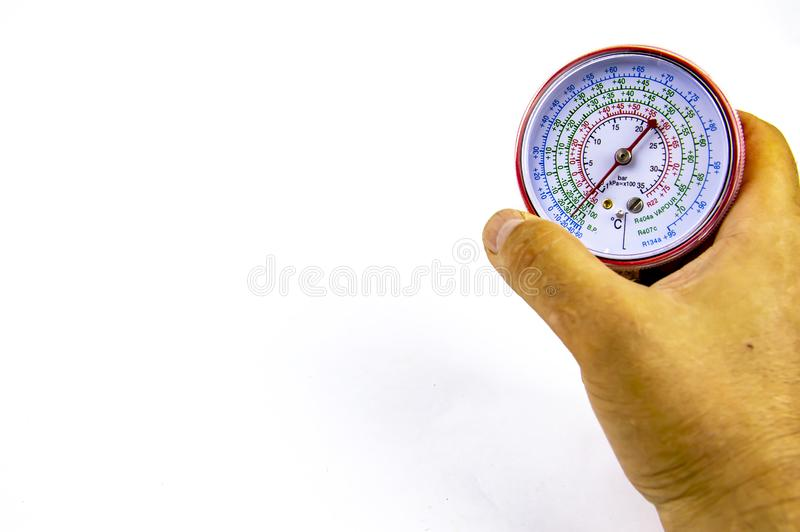 Manômetro que mede a pressão do gás para o reparo dos refrigeradores na mão imagens de stock royalty free