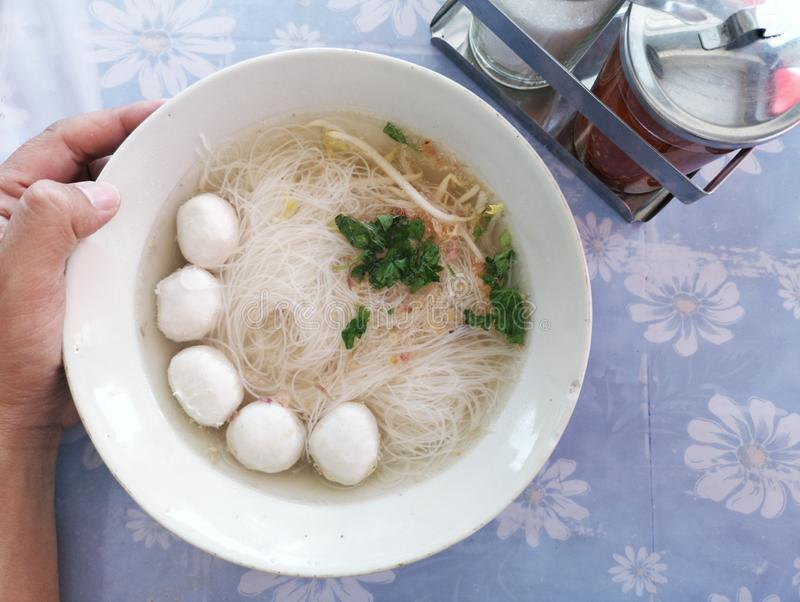 man hand hold thai nooddle with pork ball, on table royalty free stock image
