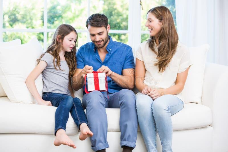 Man öppningsgåvan, medan sitta på soffan med familjen royaltyfria bilder