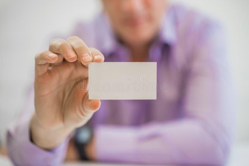 Man& x27 χέρι του s που παρουσιάζει επαγγελματική κάρτα - κινηματογράφηση σε πρώτο πλάνο που πυροβολείται στο άσπρο υπόβαθρο στοκ εικόνα