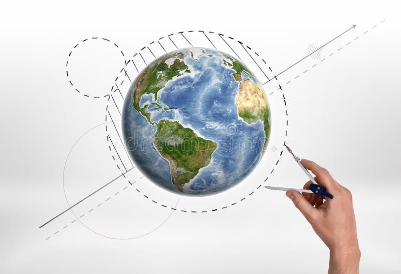 Man& x27; рука s держа компас инженерства измеряет расстояние около глобуса стоковое изображение