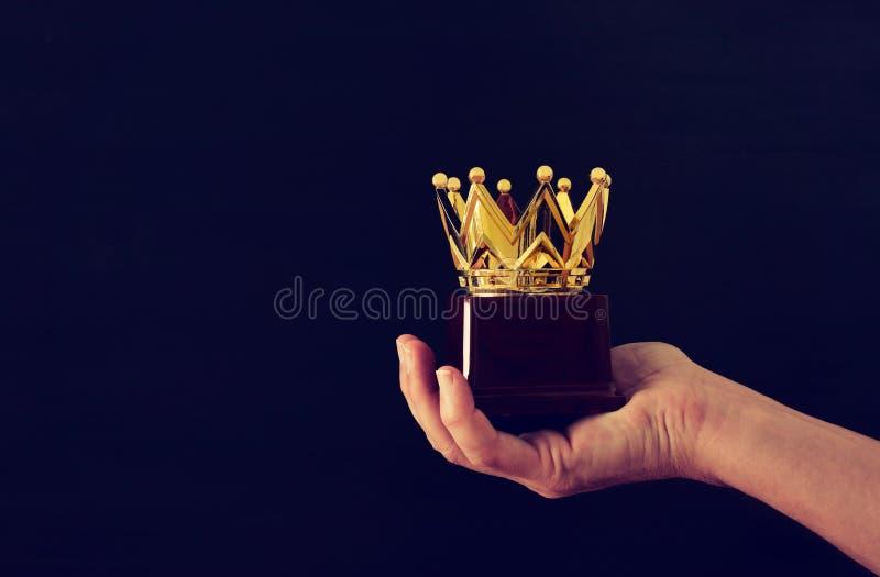 Man& x27; 拿着冠展示胜利的奖战利品或获得第一名的s手 闪烁覆盖物 图库摄影