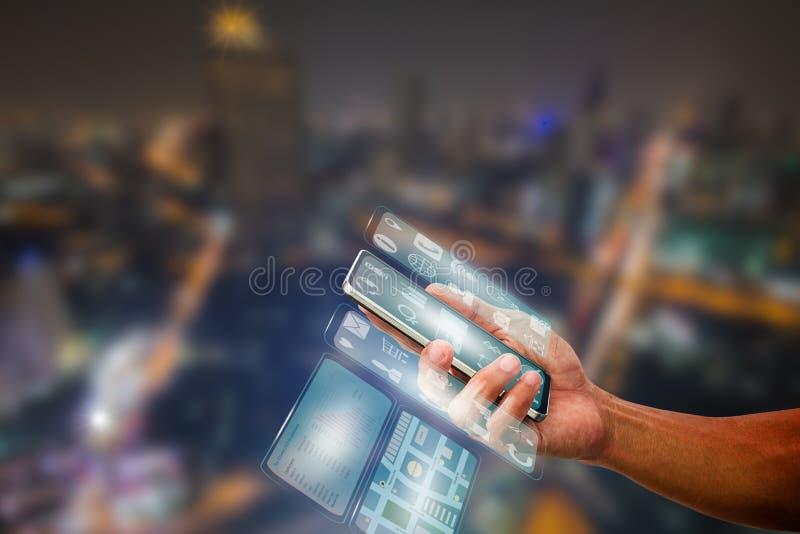 Man& x27; 拿着有透明多屏幕的s手智能手机在被弄脏的城市夜光 库存照片