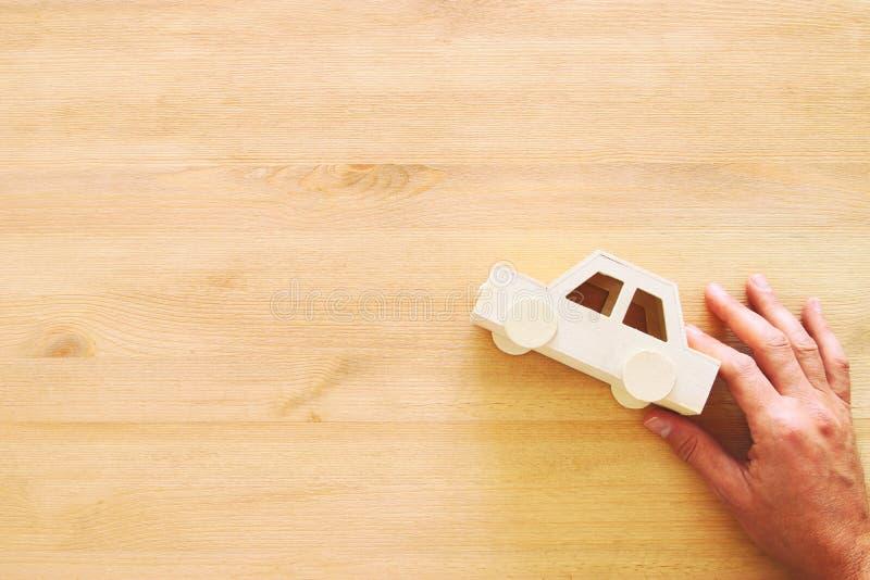 man& x27顶视图照片; 拿着在木背景的s手玩具汽车 图库摄影