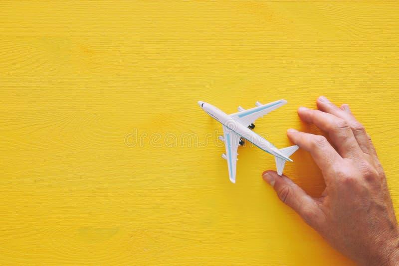 man& x27顶视图照片; 拿着在黄色木背景的s手玩具飞机 免版税库存图片