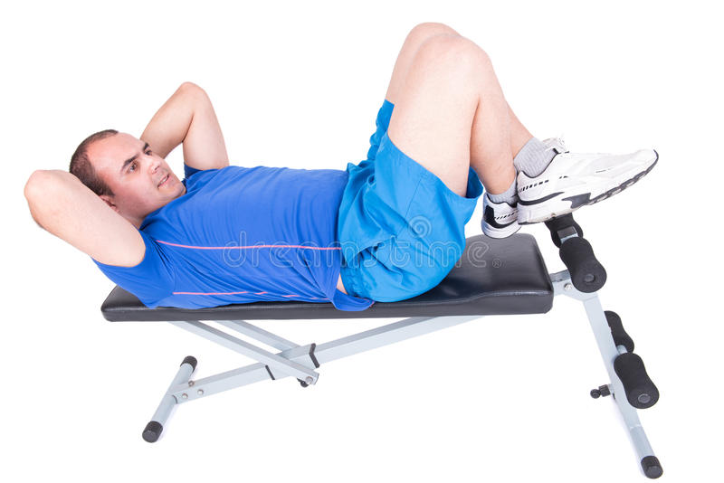 Man in abdominal bench. Man exercising on a bench crunches on white background royalty free stock photo