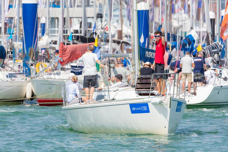 Man Aboard a Yacht During Cowes Week. Cowes, Isle of Wight; 7th August 2018; A Man in Red Polo Shirt Stands at Bow of Yacht Looking towards Camera as it Leaves royalty free stock photos