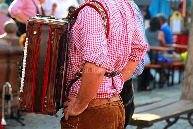 Man with an accordion, red checkered shirt and bavarian leather stock images