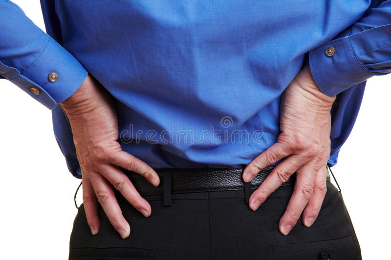 Man with aching back. Elderly businessman holding his hand to his aching back stock photos