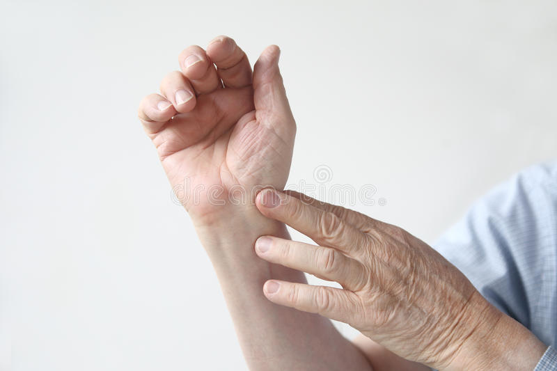 Man with an aching wrist. Man indicates where the pain is located stock photos