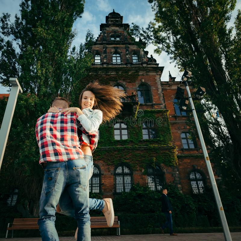 Man is actively spinning round his beautiful girlfriend with charming smile while dancing in the street. stock photos