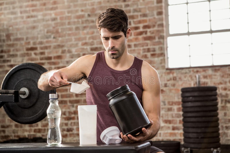 Man adding supplement from tin to bottle stock photo