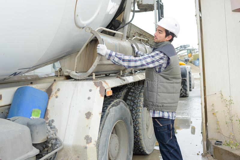 Man adjusting cement lorry. Cement royalty free stock image