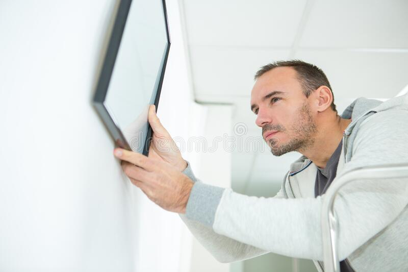 Man adjusting family picture at home. Man adjusting a family picture at home stock photo
