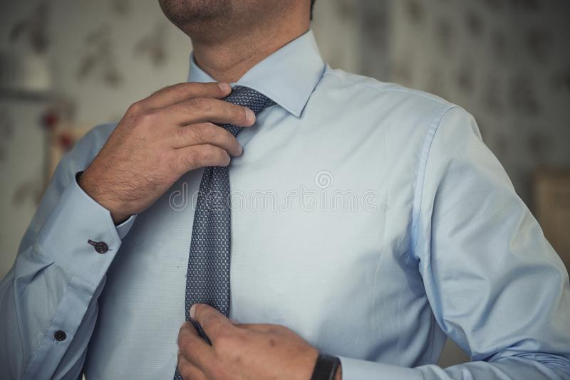 Man adjusting his necktie stock photos