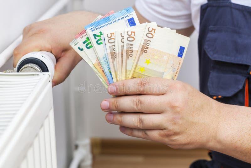 Man adjusting radiator and keep money royalty free stock photo