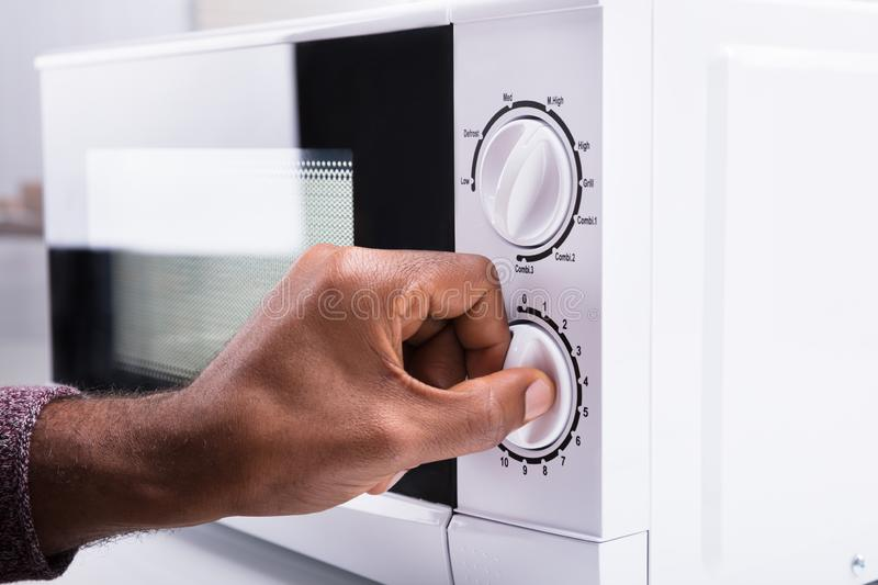 Man Adjusting Temperature Of Microwave Oven. Close-up Of A Man`s Hand Adjusting Temperature Of Microwave Oven royalty free stock photo
