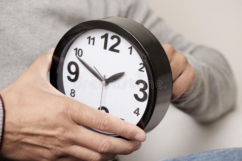 Man adjusting the time of a clock stock photos