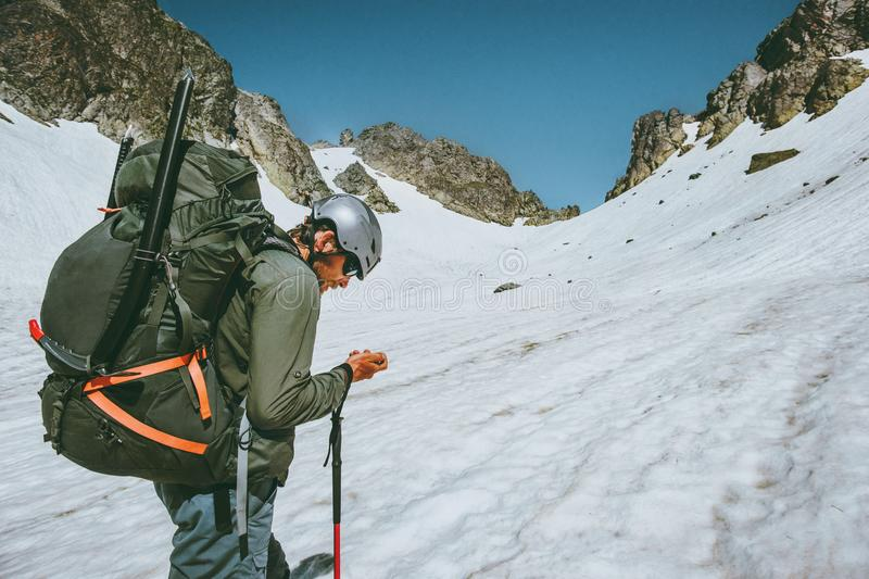 Man adventurer with gps tracker navigator checking location coordinates. Climbing in mountains expedition traveling survival lifestyle concept outdoor extreme stock image