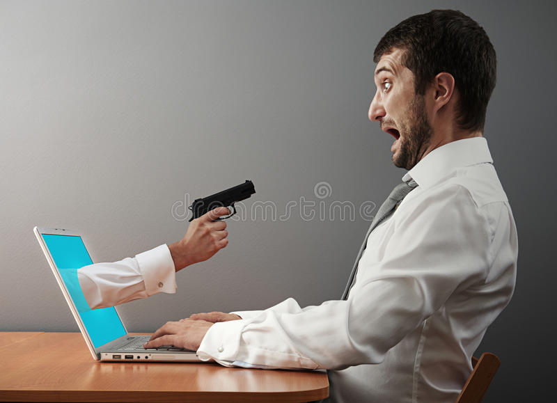 Man afraid of hand with gun. Concept photo of digital robbery. man afraid of hand with gun stock photography