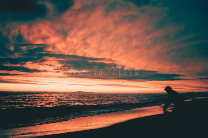 The man on the background of sunset at lake Baikal stock image