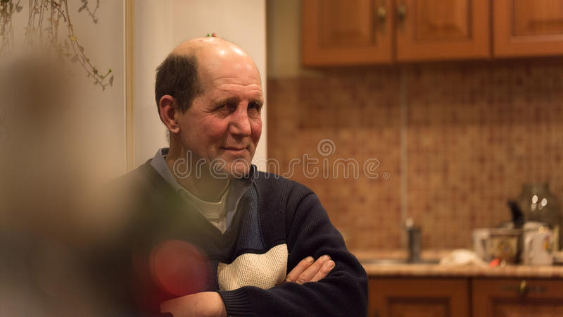 Man aged sits listening to the funny story. Man aged sits with her hands folded on his chest listening to the funny story royalty free stock image