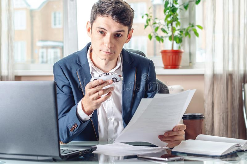 Man agent holding a car toy and documents for registration of the car. Concept of buying selling and rental of transport stock photo