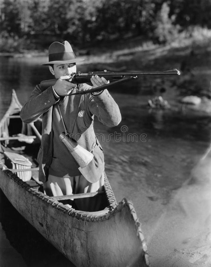 Man aiming gun from canoe. (All persons depicted are no longer living and no estate exists. Supplier grants that there will be no model release issues royalty free stock image