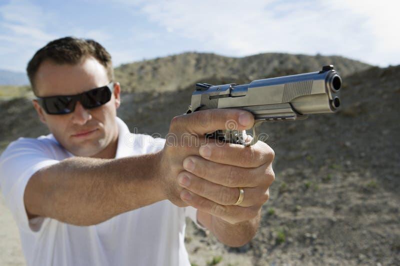 Man Aiming Hand Gun stock images