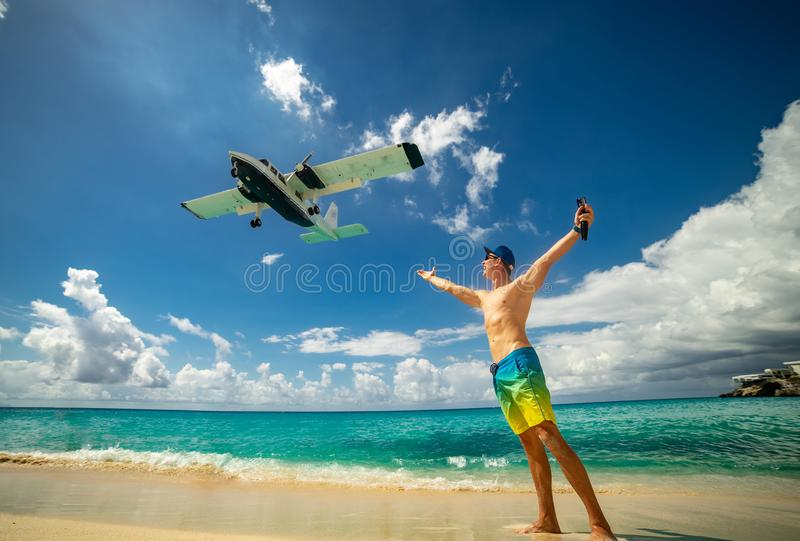 Man with airplane flying over on famous Maho beach near Princess Juliana International airport. Concept of happy. Man with airplane flying over on famous Maho royalty free stock photography